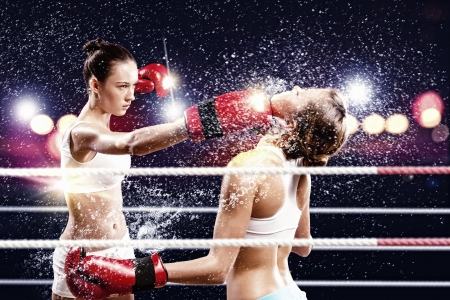 Two young pretty women boxing in ring photo