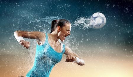 pelotas de deportes: Imagen de la joven mujer de jugador de f�tbol que golpea la bola Foto de archivo
