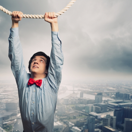 hang body: Image of businessman hanging on rope against city background Stock Photo