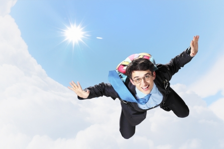 hovering: Conceptual image of young businessman flying with parachute on back Stock Photo