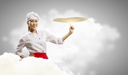 pizza dough: Asian female cook making pizza standing against color background Stock Photo