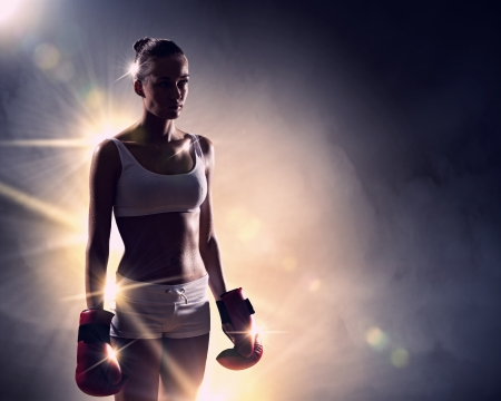 boxing sport: Young pretty boxer woman standing in light flashes