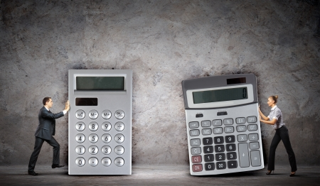Image of two businesspeople with big calculators photo