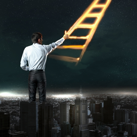 Image of young businessman standing with back drawing ladder photo