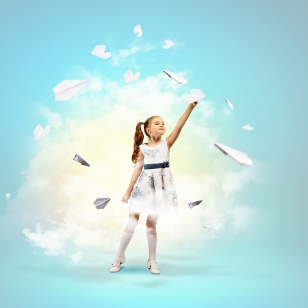 Image of little pretty girl playing with paper airplane photo
