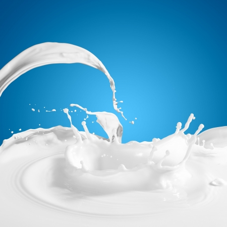 色の背景に白いミルク スプラッシュを注ぐ 写真素材