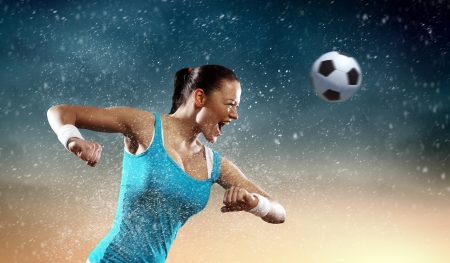 soccer players: Image of young woman football player hitting ball Stock Photo