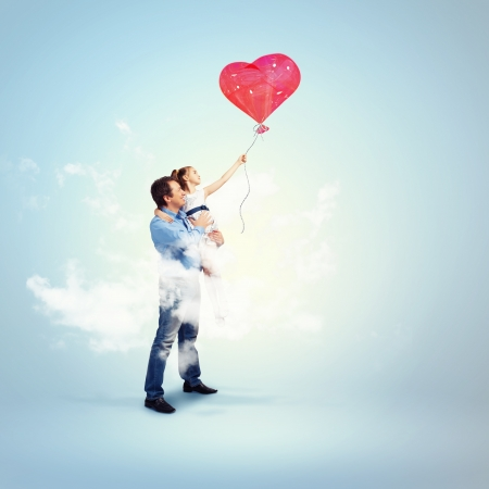 fatherhood: Image of happy father holding his daughter and a red heart baloon Stock Photo