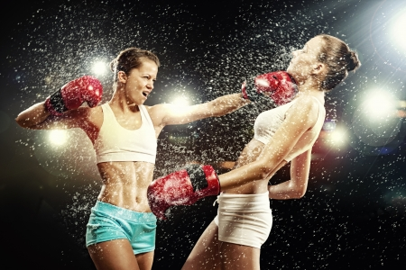 Two young pretty women boxing standing against flashes background photo