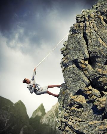 急な登山ロープにぶら下がっている実業家