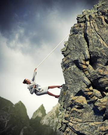 zakenvrouw klimmen steile berg opknoping op touw