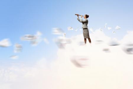marketanalyze: Image of businesswoman looking in telescope standing atop of cloud