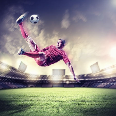 football player in red shirt striking the ball at the stadium photo
