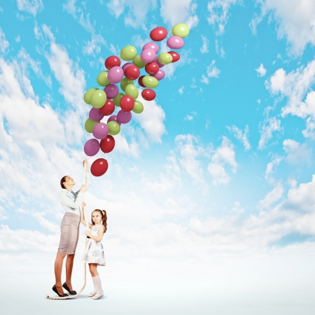 Image of little cute girl and mother with bunch of color balloons photo