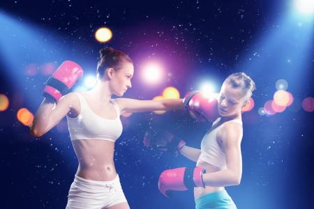 2 人の若いきれいな女性のボクシングの点滅背景に対して立っています。