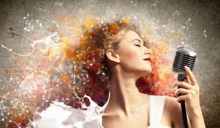 m�sico: Imagen de la rubia cantante femenina que sostiene el micr?fono contra el fondo de color con los ojos cerrados