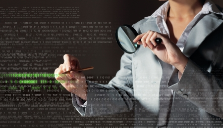 Businesswoman with magnifier glass examining binary code photo
