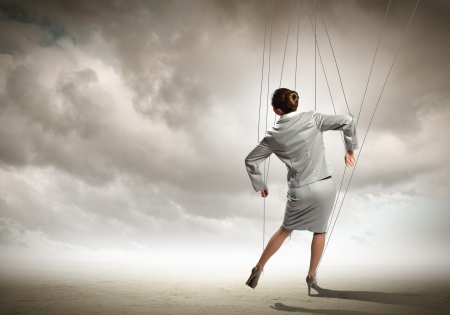manipulate: Image of businesswoman hanging on strings like marionette  Conceptual photography Stock Photo