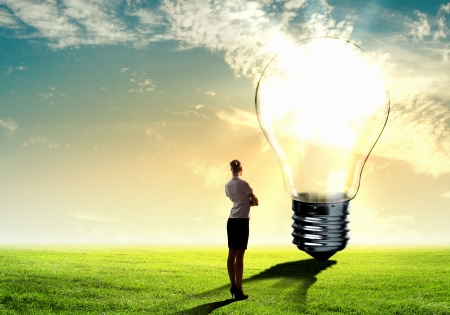 invent: Image of businesswoman looking at light bulb  Green energy concept