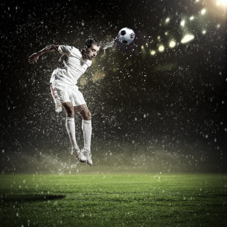 football soccer: Image of football player at stadium hitting ball