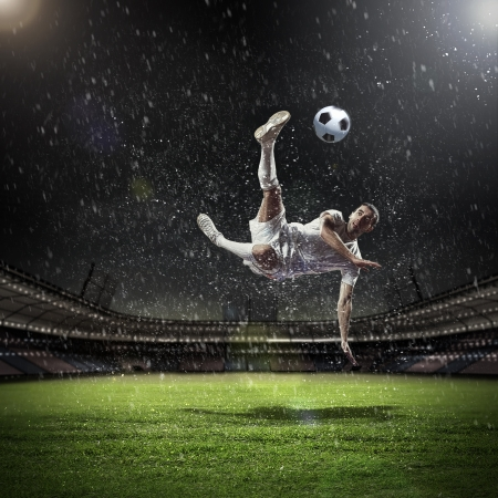 soccer players: Image of football player at stadium hitting ball