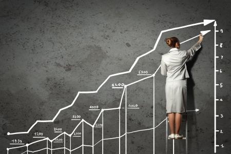 economie: Afbeelding van zakenvrouw staande op de ladder en tekenen op de muur Stockfoto