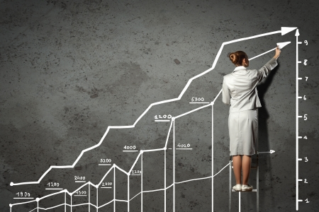 economy growth: Image of businesswoman standing on ladder and drawing on wall