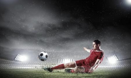 Beeld van voetballer bij stadion raken bal