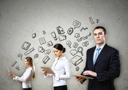 negocios internacionales: Tres j�venes en trajes de negocios con PC de la tableta en las manos