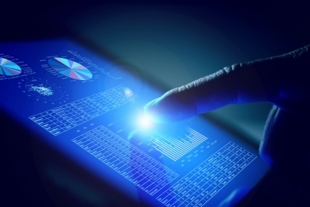 Closeup of finger touching blue toned screen on tablet-pc