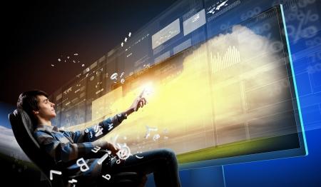 Jonge man in de leunstoel duwen icoon op media-scherm