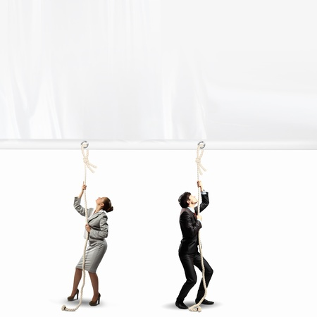 Image of two businesspeople pulling blank banner photo