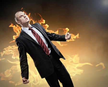 displeased businessman: Image of young businessman in anger burning in fire Stock Photo
