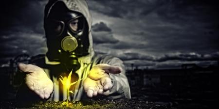 nuke plant: Hombre joven en un traje de protecci�n toca al futuro post-nuclear brotar Foto de archivo