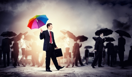 Image of pretty businessman with umbrella walking in crowd of people photo