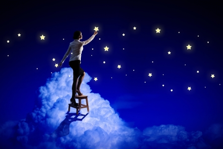 Image of young woman lighting stars in night sky photo