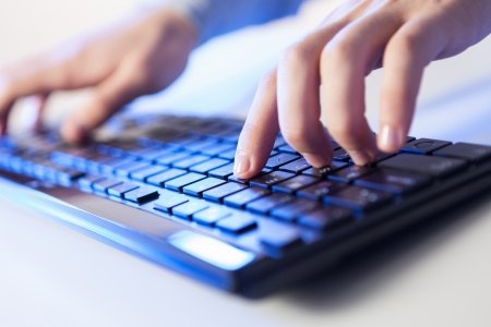 Click  Hands of a man on a keyboard with blue backlighting  photo
