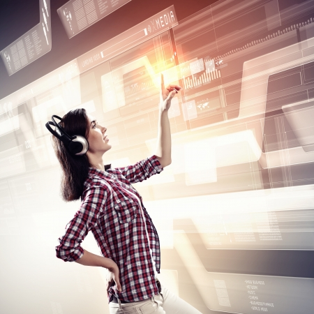 Image of young woman with headphones touching virtual screen Stock Photo - 20149749