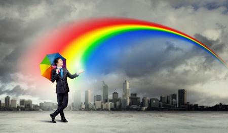 建物の上に傘を持つ黒のスーツのビジネスマン