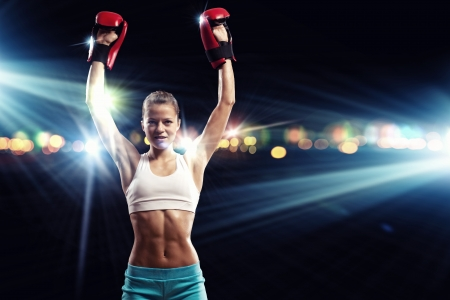 Young pretty boxer woman standing in light flashes photo