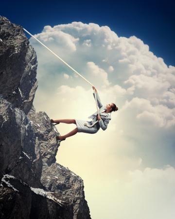 alpinism: businesswoman climbing steep mountain hanging on rope