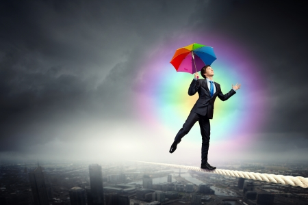 Businessman in black suit with umbrella balancing on rope photo