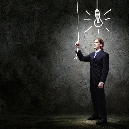 Beeld van zakenman in zwart pak tegen een donkere achtergrond