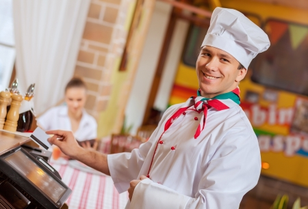 Image of handsome chef inserting card in terminal Stock Photo - 20207650
