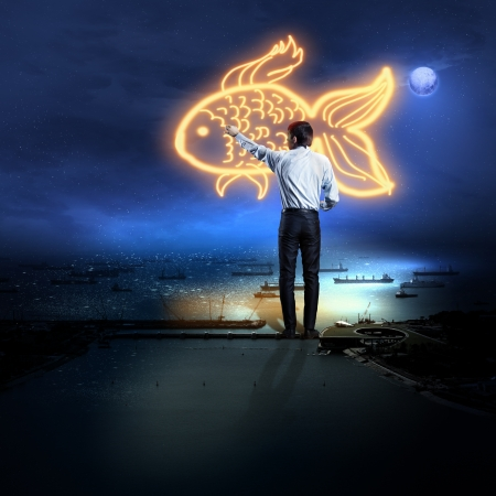 Back view of businessman drawing gold fish photo