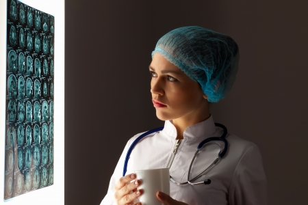 Image of attractive woman doctor looking at x-ray results Stock Photo - 20207533