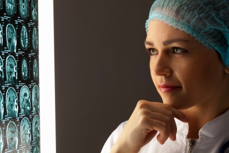Image of attractive woman doctor looking at x-ray results Stock Photo - 20207569