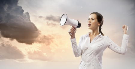 Image of young businesswoman screaming in megaphone photo