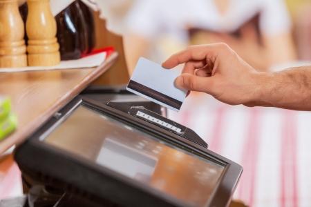 tarjeta de credito: Imagen de primer plano de las manos masculinas cajero con tarjeta de