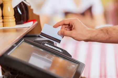electronic devices: Close-up image of cashier male hands holding card